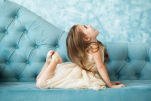 beautiful-girl-in-beige-dress-lies-on-blue-couch-and-tries-to-reach-her-head-with-feet_1304-3310
