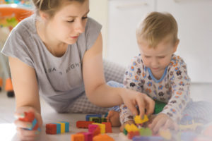 boy-with-mom-playing-in-colorful-building-kit_1321-406